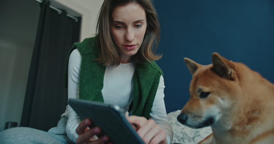 Low Angle View of Young Woman Sitting on Bed at Home with Dog Nearby. She Holds Tablet While Pointing to Screen and Stroking Her Dog. Wonderful Moments of Animal-Human Friendship. Slow Motion Shot   Shutterstock HD Video #1053186638