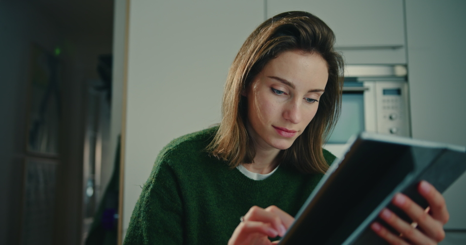 Close-Up View of Young Woman Sitting in Kitchen at Home and Using Tablet. Smiling Female Freelance Typing Messages on Mobile Device. Online Communication and Connection Concept. Slow Motion Shot | Shutterstock HD Video #1053186644