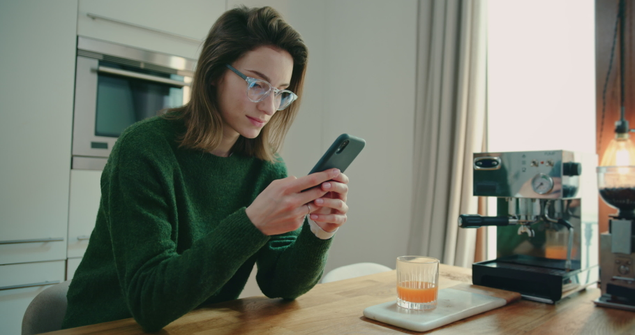 Young Smiling Woman Wearing Glasses and Green Sweater Sitting in Kitchen at Home and Typing on Smartphone, Staying in Touch with Friends and Family. Technology Brings People Together. Slow Motion Shot | Shutterstock HD Video #1053186647