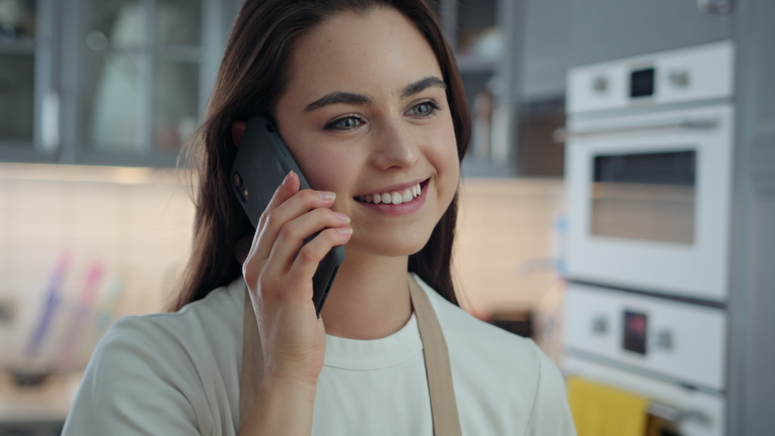 Portrait of Young Attractive Woman Smiling and Talking on Phone While Being in Kitchen at Home. Girl Using Smartphone to Communicate and Stay in Touch with Her Friends and Family. Slow Motion Shot   Shutterstock HD Video #1053186650