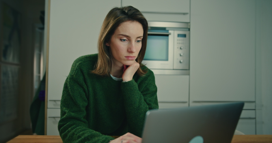 Young Woman Sitting at Table in Kitchen and Typing on Laptop Keyboard. Female Student Using Portable Computer for Study and Work. Social Networking and Communication Concept. Slow Motion Shot   Shutterstock HD Video #1053186653