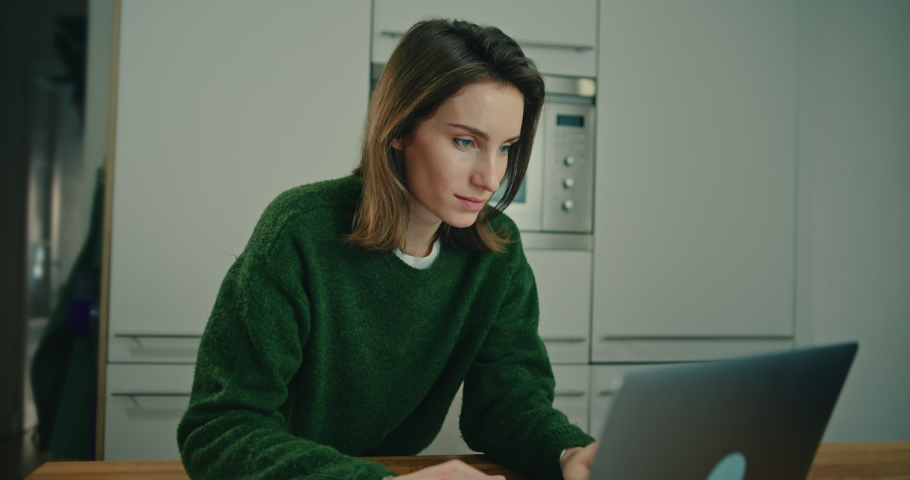 Young Woman Sitting at Table in Kitchen and Typing on Laptop Keyboard. Female Student Using Portable Computer for Study and Work. Social Networking and Communication Concept. Slow Motion Shot | Shutterstock HD Video #1053186653