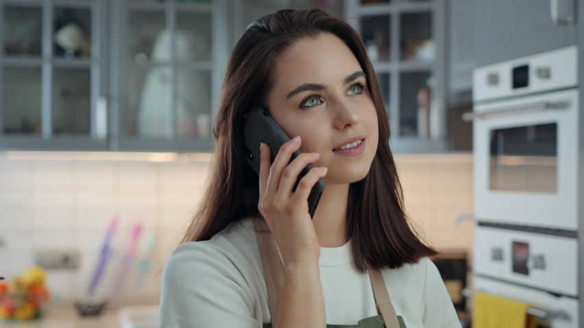 Portrait of Young Attractive Woman Talking on Phone While Being in Kitchen at Home. Girl Using Mobile Device to Communicate and Stay in Touch with Her Friends and Family. Slow Motion Shot | Shutterstock HD Video #1053186656