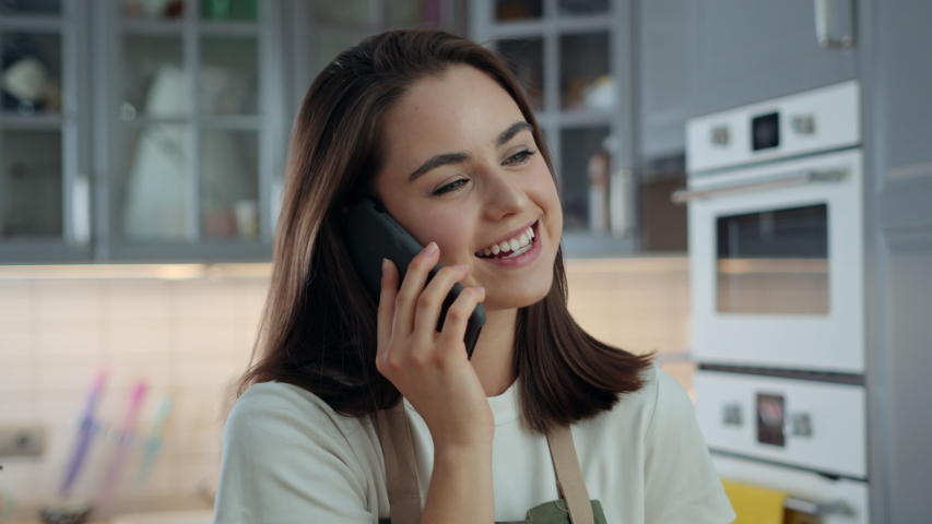 Portrait of Young Attractive Woman Talking on Phone While Being in Kitchen at Home. Girl Using Mobile Device to Communicate and Stay in Touch with Her Friends and Family. Slow Motion Shot   Shutterstock HD Video #1053186656
