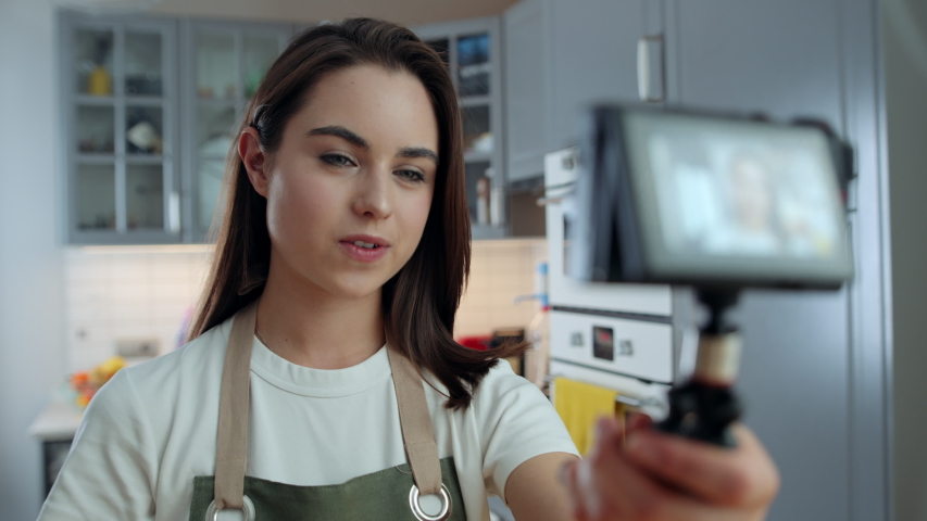 Young Woman Holding Digital Camera and Showing Artichoke While Recording Video about Cooking Healthy Food Using Vegetables. Female Freelancer Filming for Her Vlog in Kitchen at Home. Slow Motion Shot | Shutterstock HD Video #1053186659