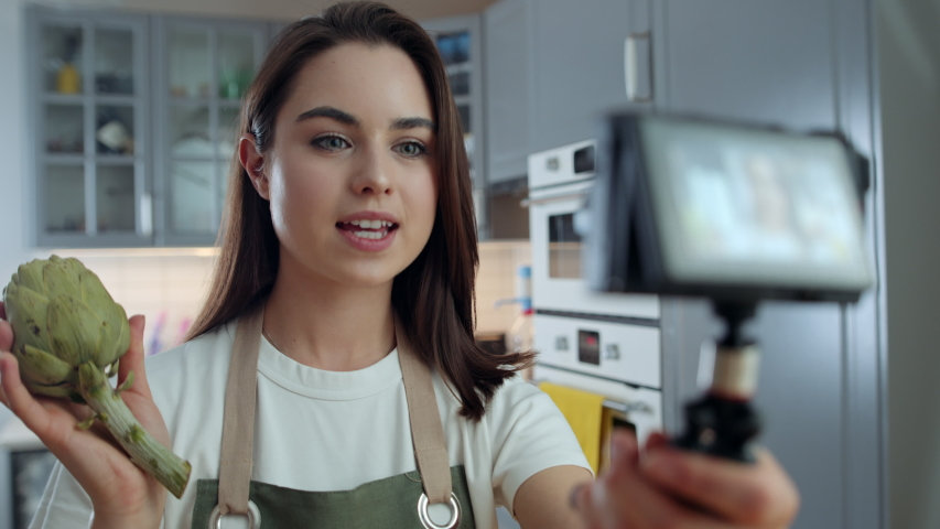 Young Woman Holding Digital Camera and Showing Artichoke While Recording Video about Cooking Healthy Food Using Vegetables. Female Freelancer Filming for Her Vlog in Kitchen at Home. Slow Motion Shot   Shutterstock HD Video #1053186659