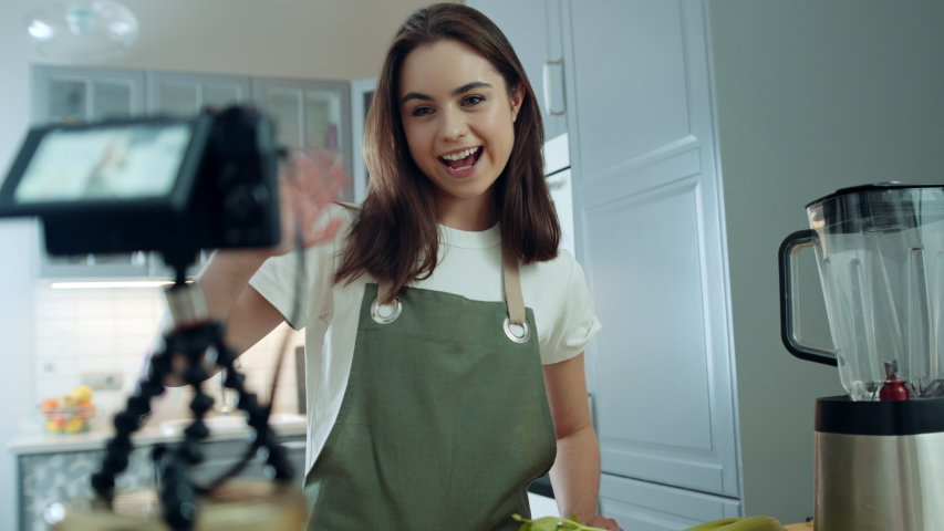 Attractive Caucasian Girl Recording Video Using Digital Camera on Cooking Healthy Food. Young Female Vlogger Filming in Kitchen at Home, Waving Hello and Talking to Her Audience. Slow Motion Shot   Shutterstock HD Video #1053186668