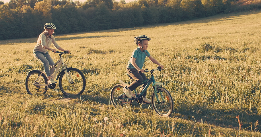 Mother and son ride a bike. Happy cute boy in helmet learn to riding a bike in park on green meadow in summer day at sunset time. Family weekend. 4K video, Slow motion | Shutterstock HD Video #1053186947
