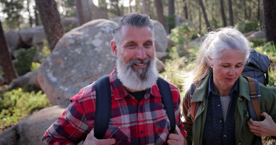 Close up senior caucasian couple hiking with backpacks at forest