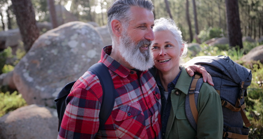 Close up senior couple hugging posing for photo in forest