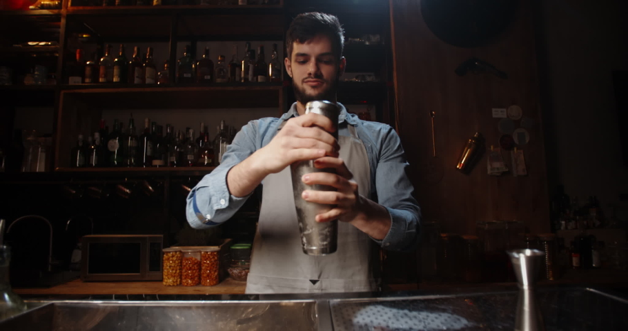 Cool professional caucasian bartender making a cocktail, muddling ice with beverage in his shaker. Authentic barman making alcohol drink using special equipment 4k footage