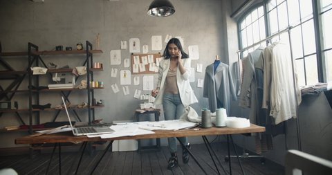 Successful female fashion designer working at her office, picking clothes while dialing or recording voice message for customer or making order - fashion concept 4k footage
