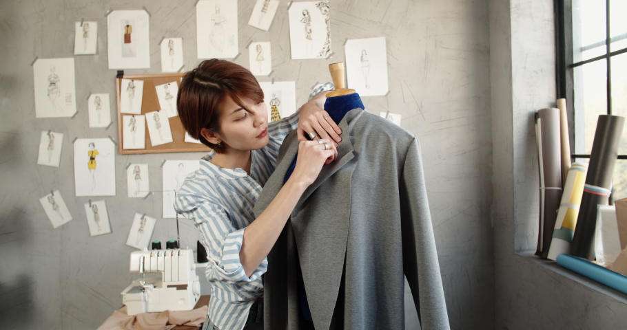 Hipster female fashion designer working with clothes on mannequin in her office, picking the best option for her customers - fashion, small business concept 4k footage