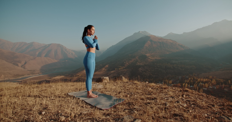 Athlete training yoga. Young healthy girl having a yoga meditation session in mountains during sunrise - healthy lifestyle, zen concept 4k footage