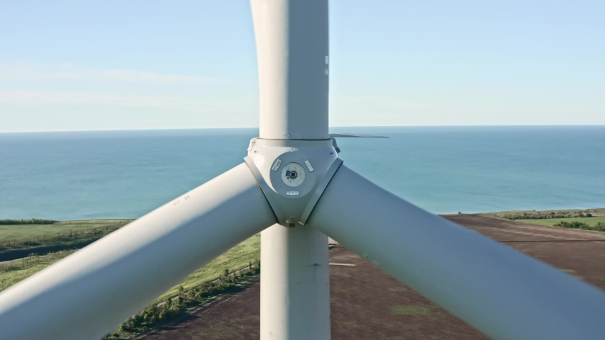Close up of a wind turbine. Aerial top view wind turbine, moving above the white modern construction of the wind turbine is device that converts winds kinetic energy into electrical energy.