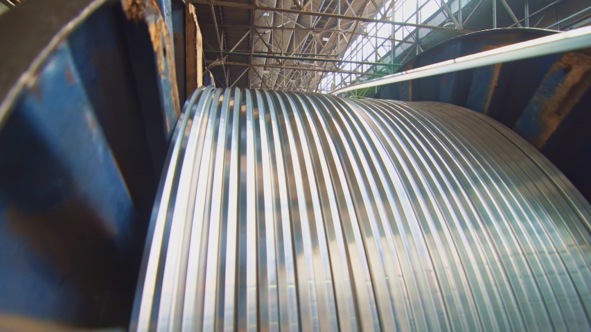 A huge bobbin unwinds a wire in a cable factory. Products are used in energy, transport, construction, engineering, nuclear, defense, oil and gas industries. | Shutterstock HD Video #1053192140