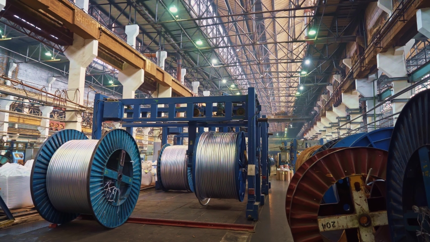 Cable factory. Metal, optical, copper, power wires are wound on huge coils. Products are used in the energy, transport, construction, engineering, nuclear, defense, oil and gas industries. | Shutterstock HD Video #1053192179