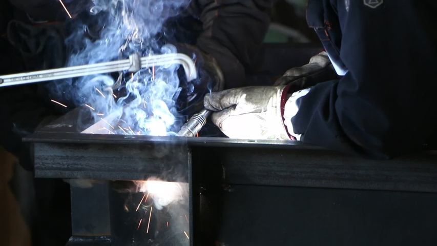 A highly skilled welder welds a metal structure at an assembly plant. Welding process 135.  | Shutterstock HD Video #1053193970