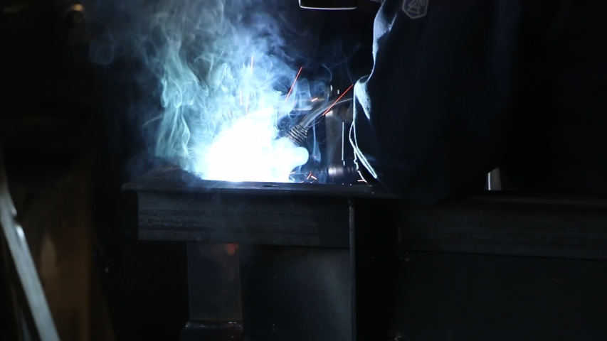 A highly skilled welder welds a metal structure at an assembly plant. Welding process 135.  | Shutterstock HD Video #1053193976