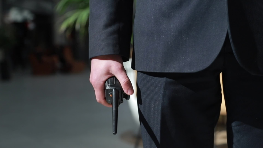 The guard holds a walkie-talkie in his hand. Hand of a security guard holding an intercom in his hand. Royalty-Free Stock Footage #1053195392