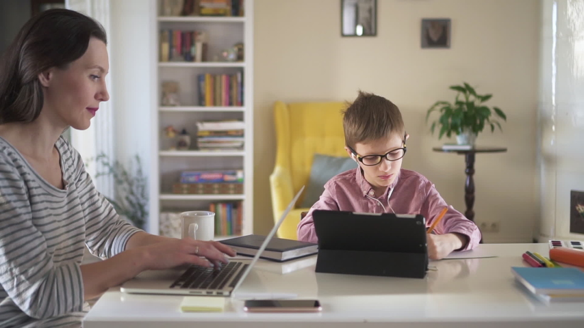 Caucasian woman is working with laptop and boy doing homework at table in apartment spbd. Young mother works remotely and looks at computer screen, her son writes in notebook while sitting at desk in | Shutterstock HD Video #1053197417