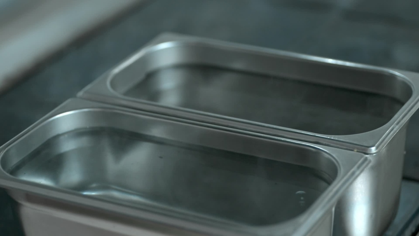 Water boiling in steel metallic container lrrl. empty tray ready to fill with food meals. concept catering, eatery, public canteen. cooking in smorgasbord restaurant. | Shutterstock HD Video #1053197471
