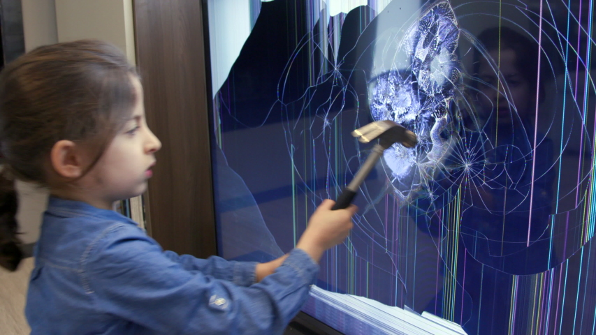 Upset little girl smashing LCD TV set screen with hammer. Angry female child hitting television monitor with heavy object for rage and violence | Shutterstock HD Video #1053199898