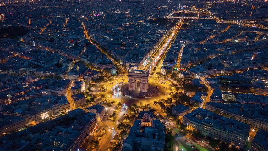Night time illumination paris city center triumph arch traffic circle street aerial timelapse panorama 4k france