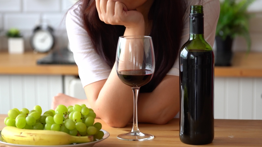 Young woman drinking red wine at table. Close up of adult female takes glass of wine, sitting in kitchen. Royalty-Free Stock Footage #1053201431