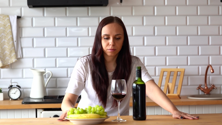 Young woman drinking red wine at table. Close up of adult female takes glass of wine, sitting in kitchen. Royalty-Free Stock Footage #1053201437