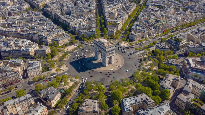 Flight over paris city sunny day famous triumph arch traffic circle streets aerial timelapse panorama 4k france