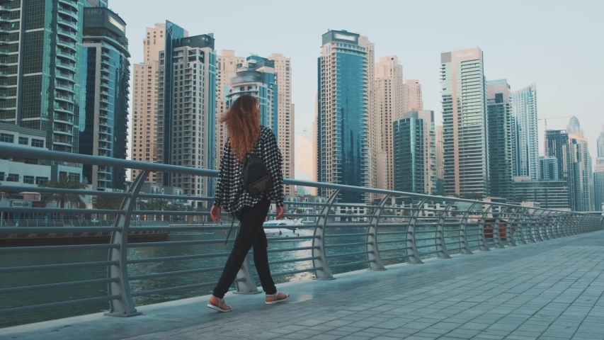 Young redhaired woman tourist walking along promenade Arab city Dubai Marina. Blue white facade modern high-rise buildings skyscrapers harmony with color sky, water. Plaid shirt, backpack. UAE 4k 2020 | Shutterstock HD Video #1053201806