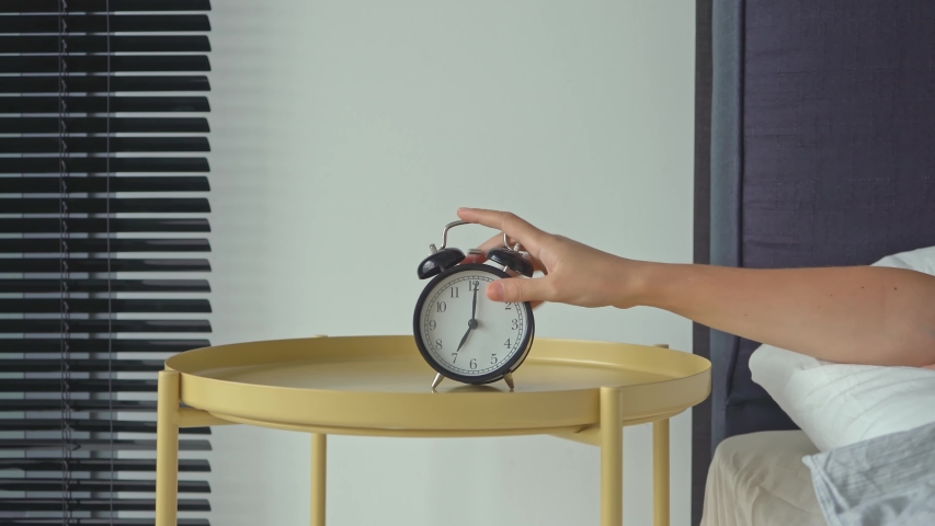 An alarm clock rings in the morning on a bedside table. The girl's hand overturns the alarm so that he shuts up. Royalty-Free Stock Footage #1053201908