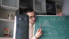 A male Caucasian online educator , holding a chalk board , teaching mathematics to his students via video call on  his smartphone mobile device