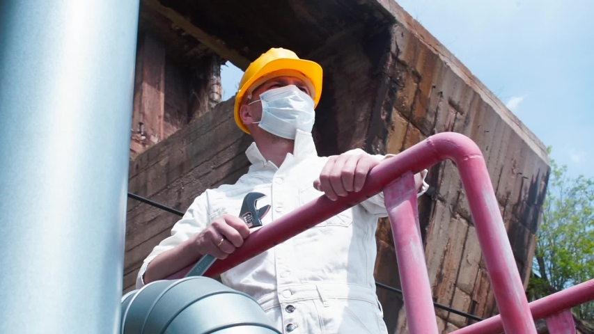 A man in a mask on his face and a helmet on his head stands at a construction site. Overhaul and maintenance of buildings and structures during quarantine COVID-19. Worker stress relaxation.