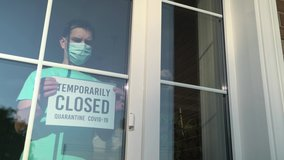 Temporary business closure. Caucasian white business owner wearing face mask attaching TEMPORARILY CLOSED sign at shop entrance due to coronavirus covid-19 epidemic outbreak over the world. 4K video