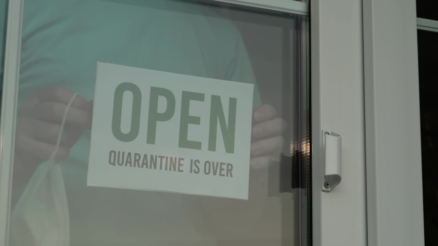 Open sign in a shop window with reflections. Small business owner walks up to the window, takes off the mask and flips the sign from closed to open, close-up. Ended the lockdown and quarantine. Royalty-Free Stock Footage #1053205832