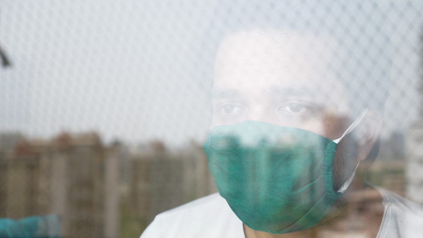 A shot of a young man through the glass window is wearing a green protective face mask and looking out. A distressed or worried patient is quarantined during Coronavirus or COVID 19 epidemic