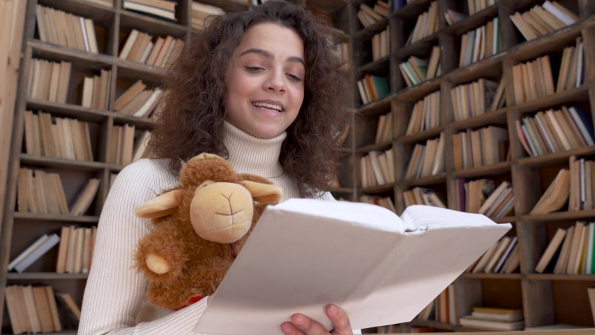 Hispanic young woman remote kids teacher reading fairy tale book teaching online. Young happy latin girl holding book and toy looking at webcam. Distance children video call zoom education concept. Royalty-Free Stock Footage #1053207089