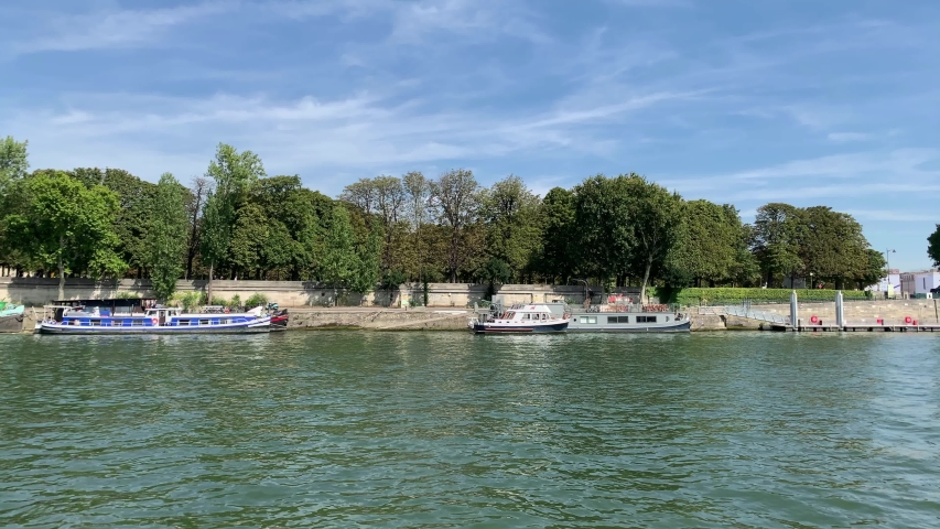 Footage of moored boats and trees by Seine river in Paris. It is a sunny summer day. Camera moves forward.   Shutterstock HD Video #1053209321