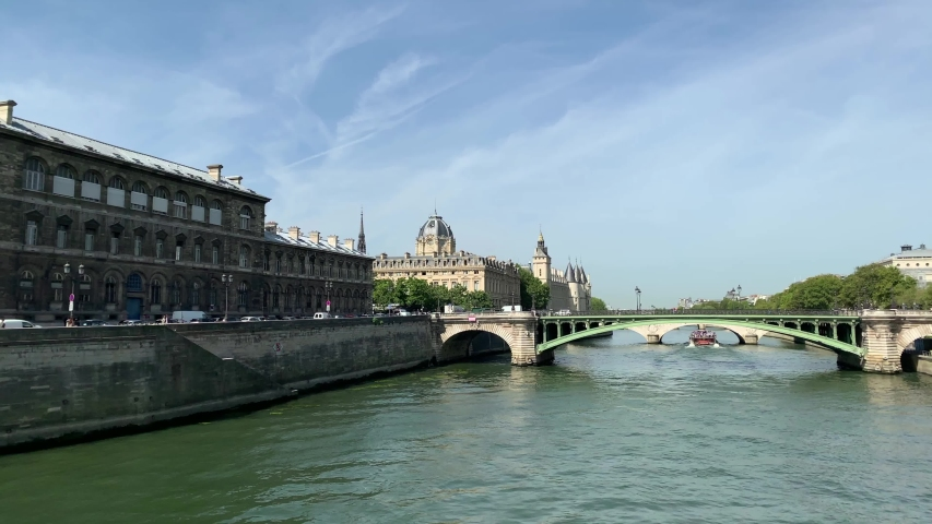 """Footage of people walking and running by Seine river and """"Pont Notre-Dame"""" bridge in Paris. It is a sunny summer day. Camera pans right.   Shutterstock HD Video #1053209333"""