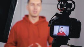 Male videoblogger filming new vlog video with professional camera at home