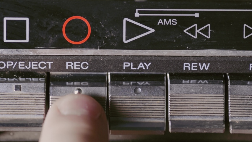 Man finger pressing some buttons on an old retro vintage cassette tape player: play, rewind, fast forward, stop