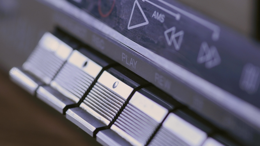 Man finger pressing some buttons on an old retro vintage cassette tape player: play, rewind, fast forward, stop | Shutterstock HD Video #1053215435