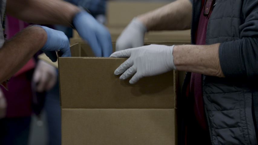 Food donation boxes going down a line of gloved volunteers during the COVID-19 pandemic   Shutterstock HD Video #1053216767