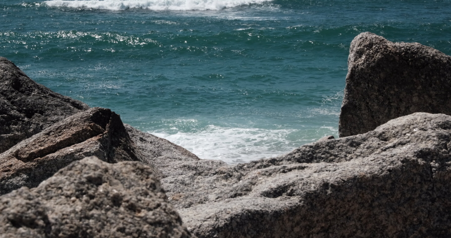 Big white waves forming and breaking on sandy beach seen through gap in rocks on sea wall in Portugal