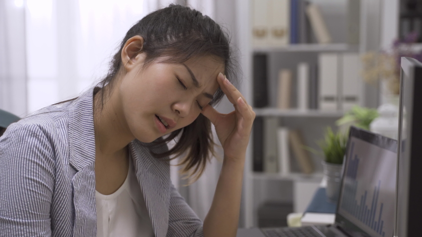 Feeling sick and tired. Frustrated young asian chinese woman employee massaging head and keeping eyes closed while sitting at working place in modern home office. illness lady worker suffer headache | Shutterstock HD Video #1053220007