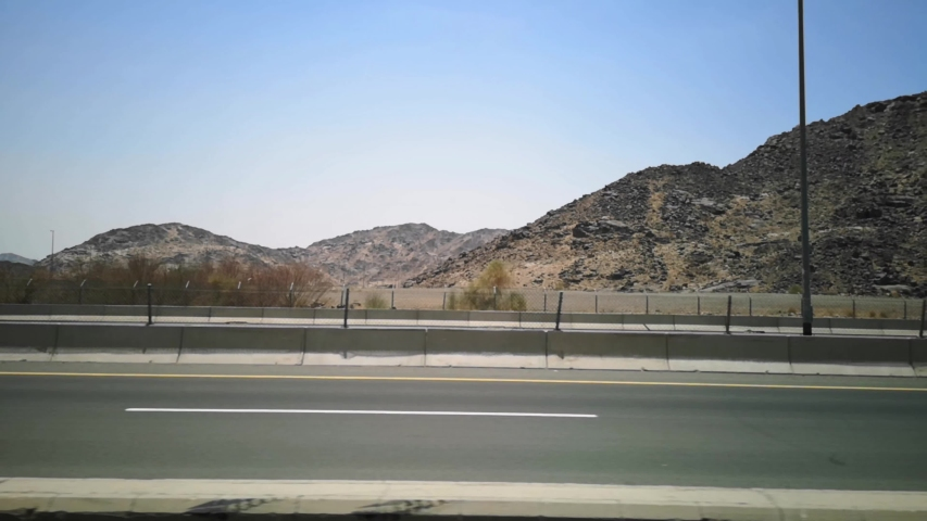 The view of the hills on the road with the background of the blue sky