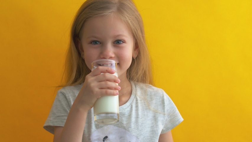 Happy girl hold glass of milk yellow background. Enjoying natural cows milk. Diet and nutrition. Healthy dieting. Good habit. Dairy products. Drink more milk