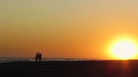 Couple watching the sunset a sunny day on sandy beach
